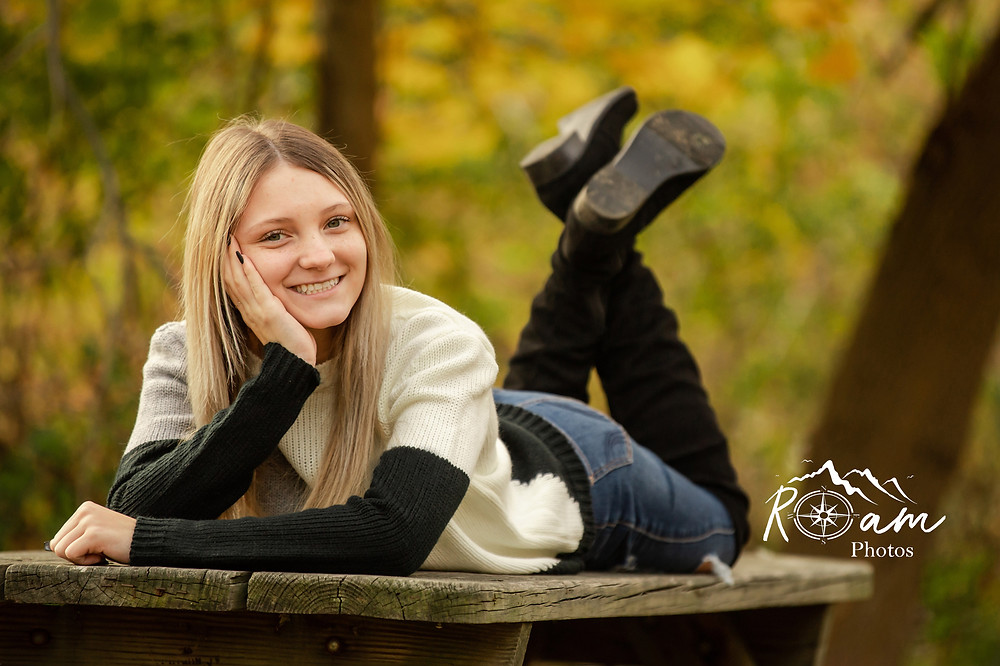 Cute young woman lying on a bench smiling