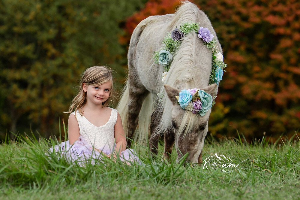 Little girl smiling as she sits in the grass while the pony unicorn eats grass.
