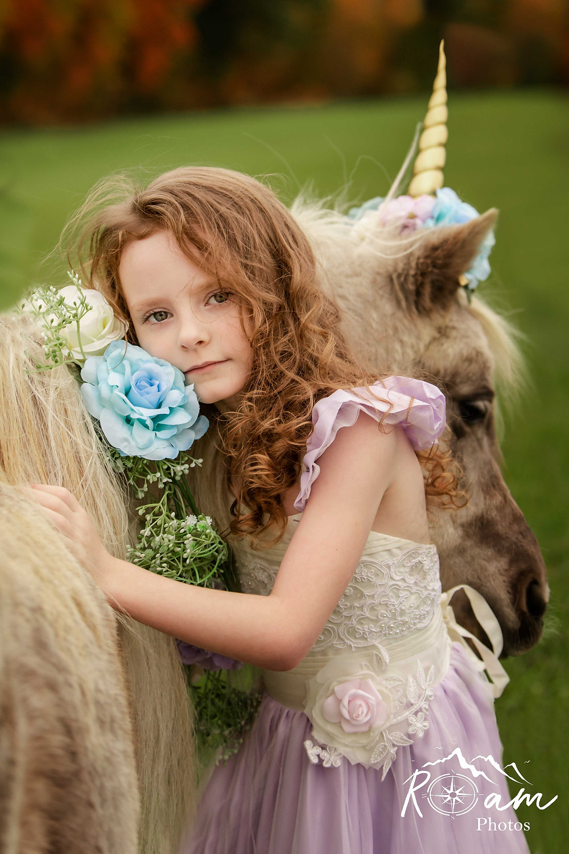 Little red headed girl hugging a unicorn pony