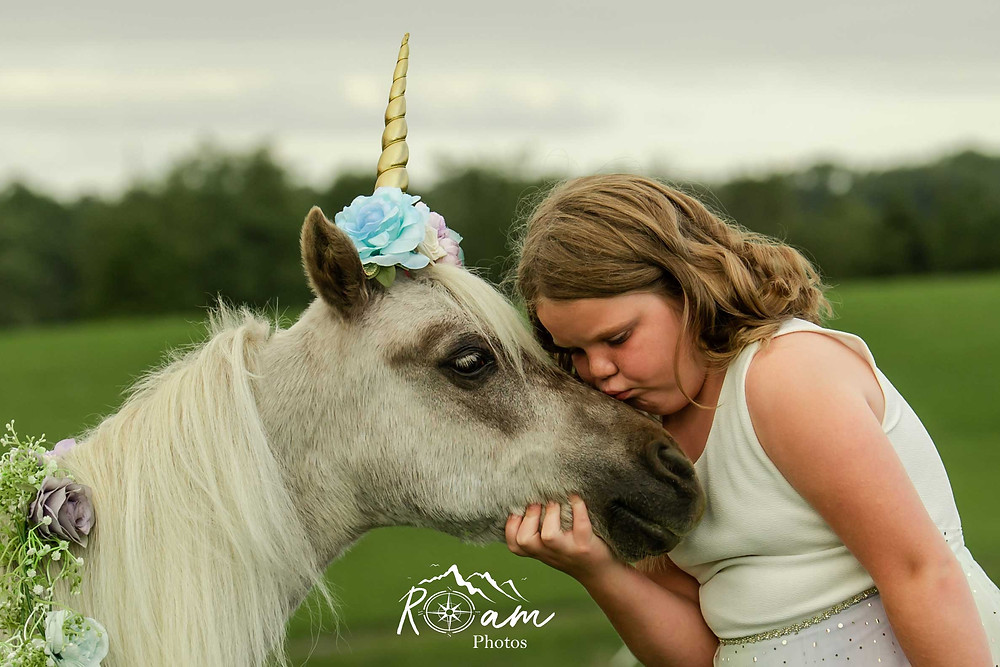Little girl kissing the pony unicorn