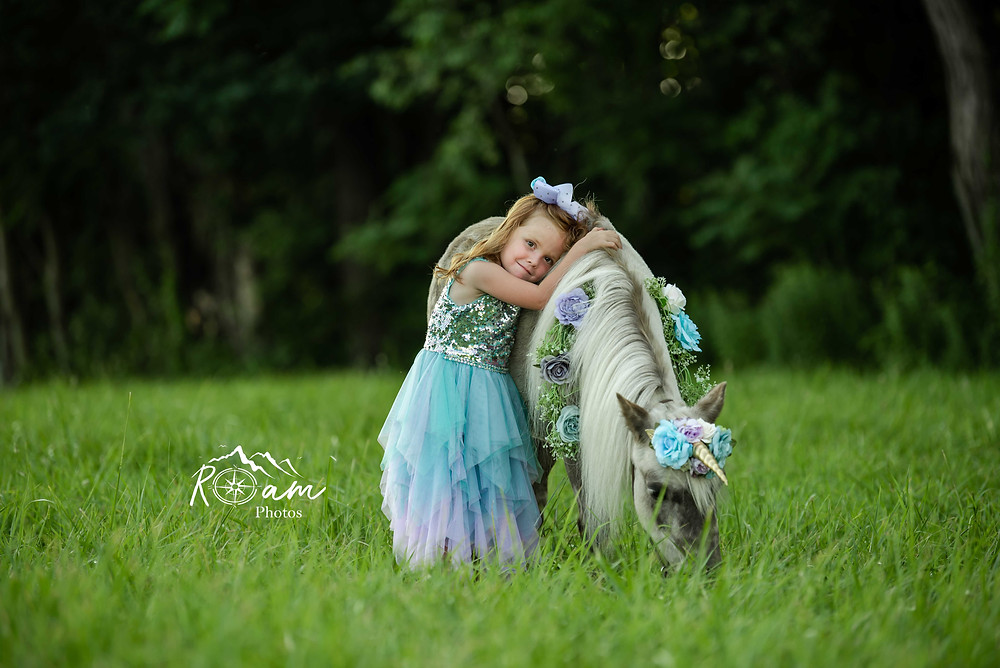 Little girl leaning on a pony as it eats grass.
