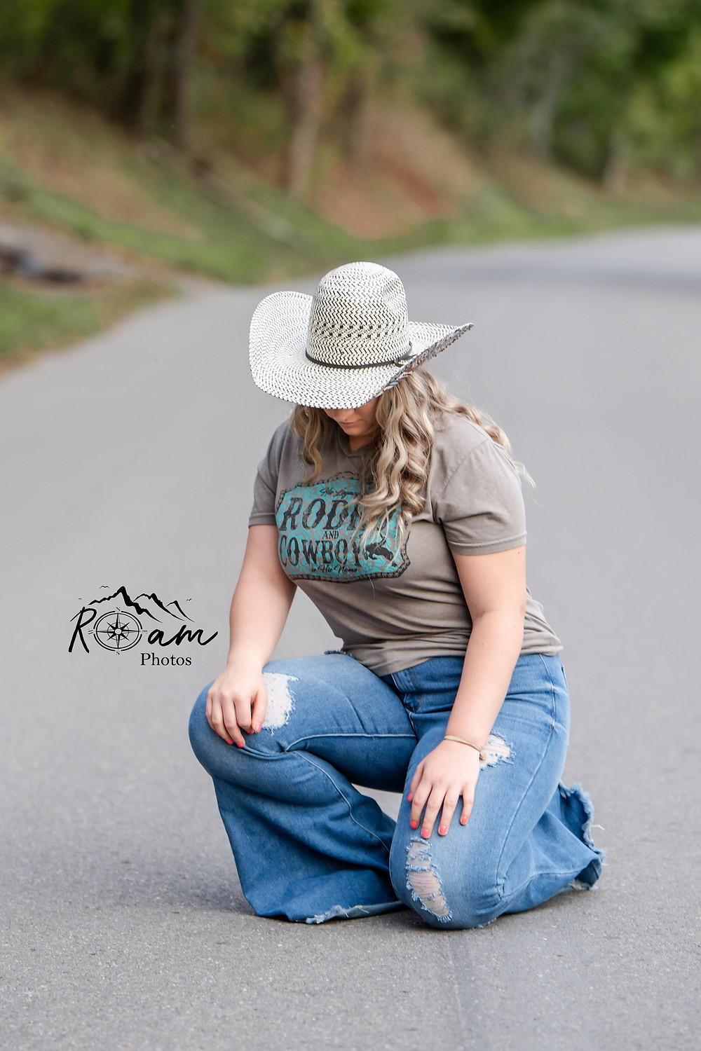 Young cowgirl kneeling in middle of a country road.