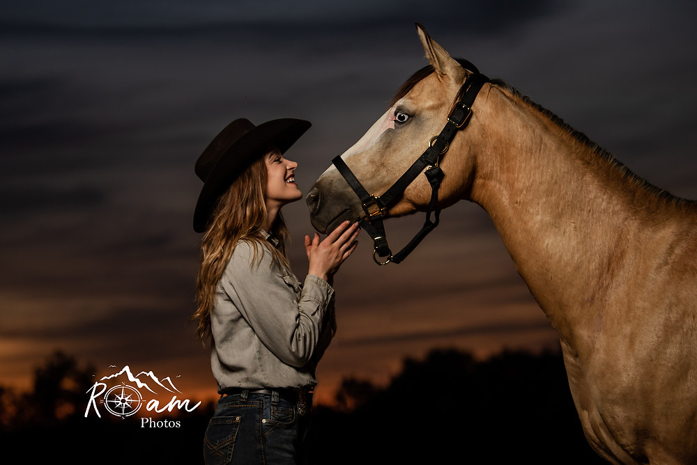 Girl looking lovingly at her horse during a sunset