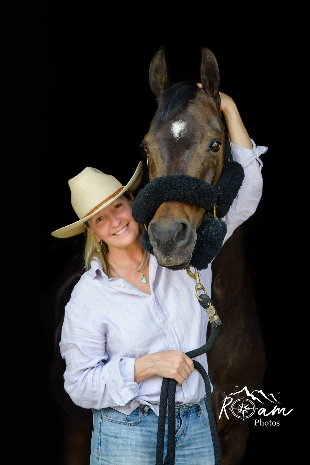 woman with cowboy hat hugging her horse