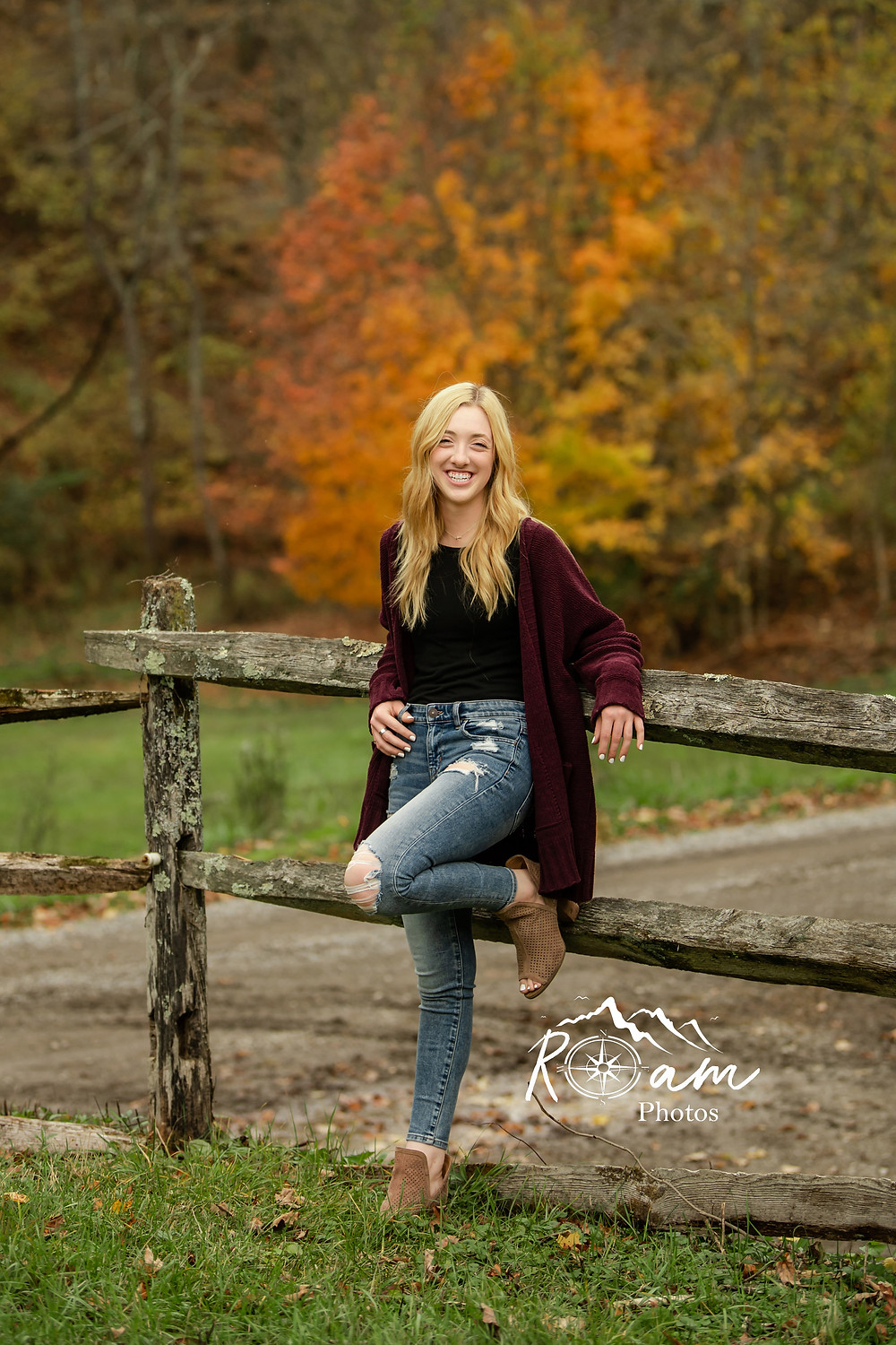 Senior photos of a young girl leaning on a fence.