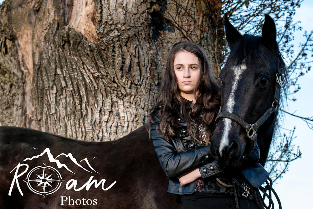 girl standing with black mare arms crossed