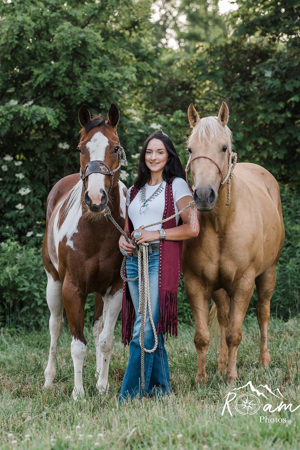 Cowgirl holding two horses.