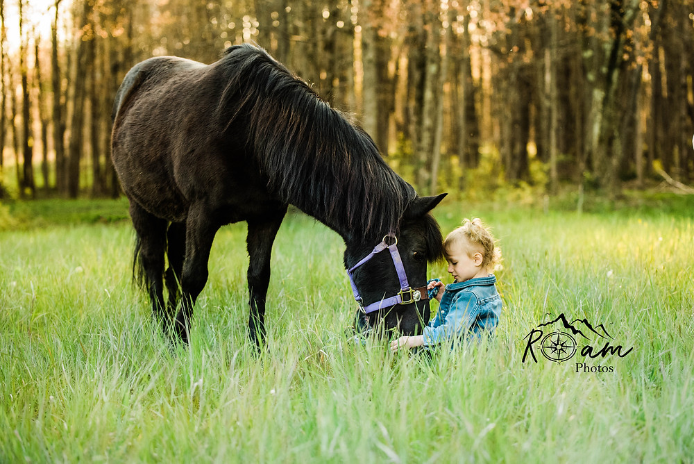 Little girl sitting in grass while pony grazes.