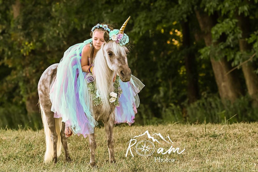 Little girl sleeping on a pony unicorn in princess dess
