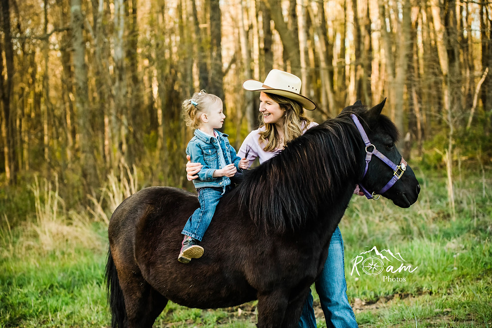 Little girl on pony with mom hugging her.