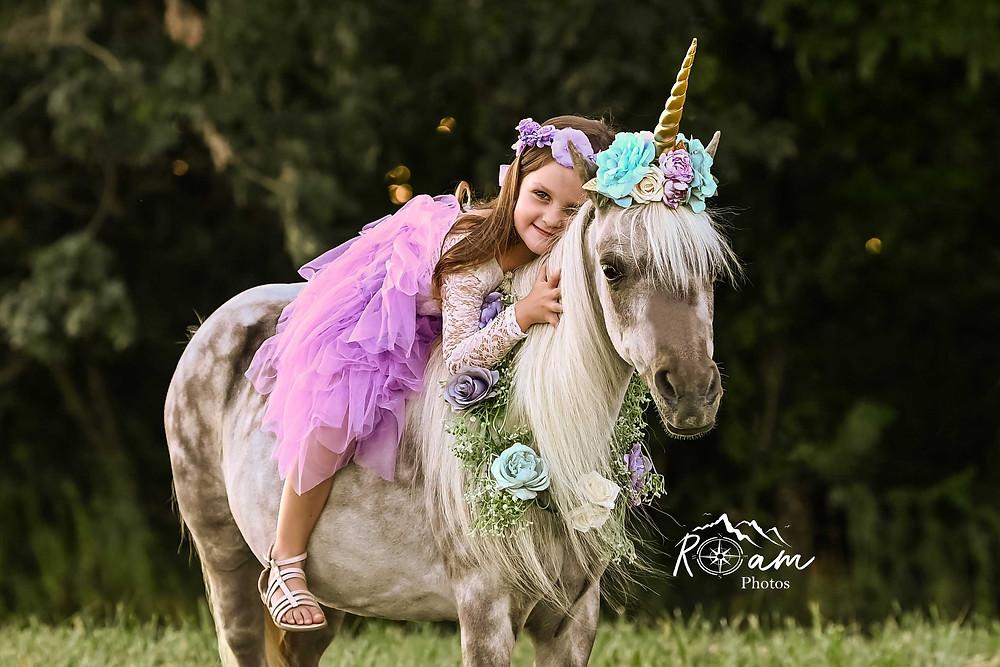 Little girl lying on a pony unicorn smiling