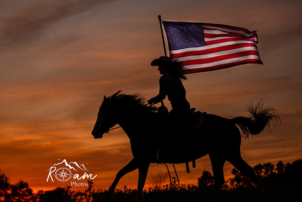 silhouette of girl running on horse with American Flag.