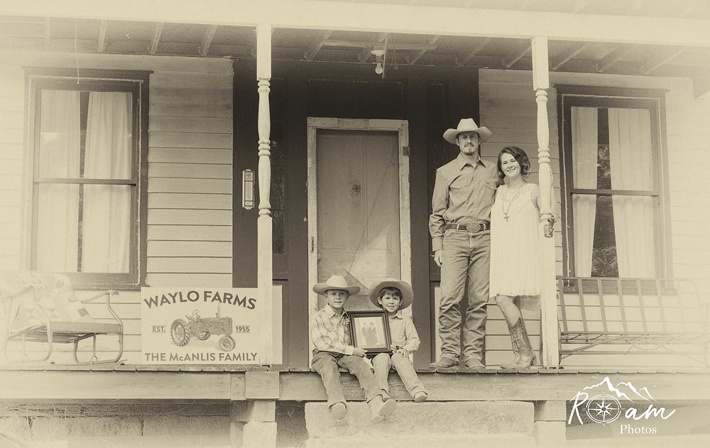 Family holding great grandparents photo on their old farm house.