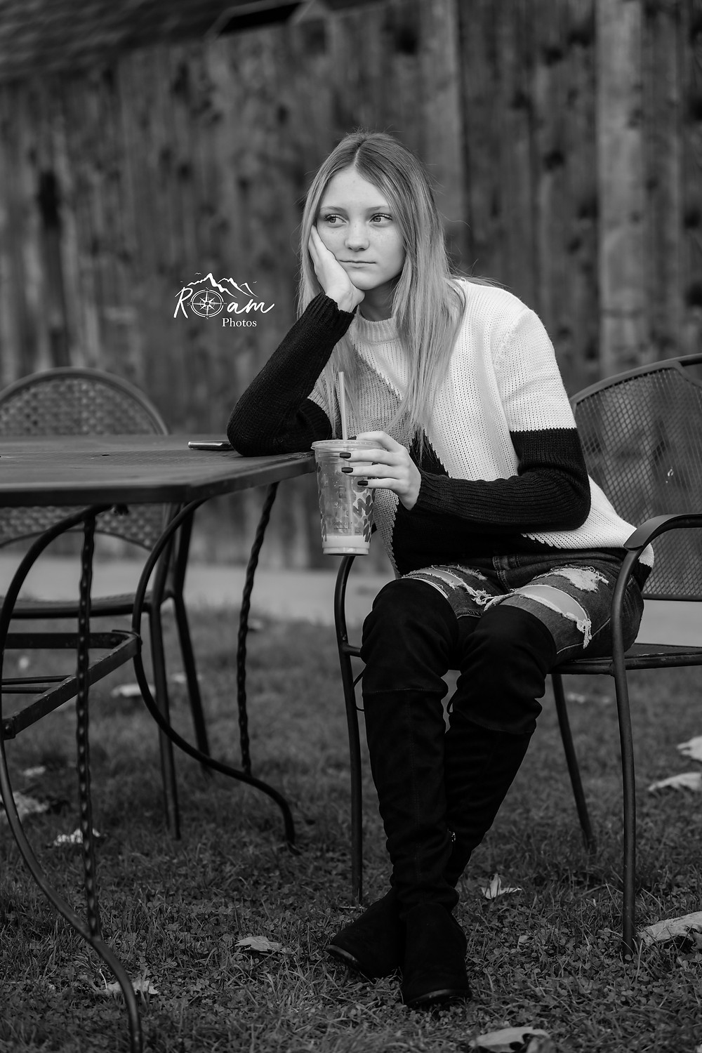 Young woman sitting at a park table drinking Dunkin Donuts