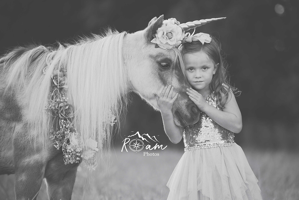 Little girl hugging a unicorn pony in black and white