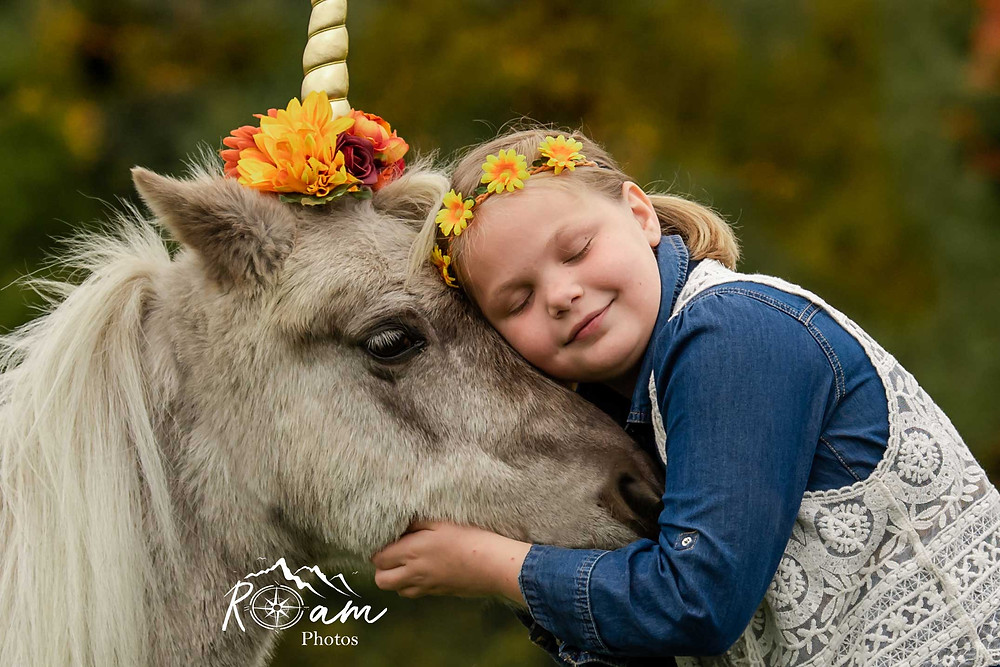 Little girl hugging a pony unicorn.
