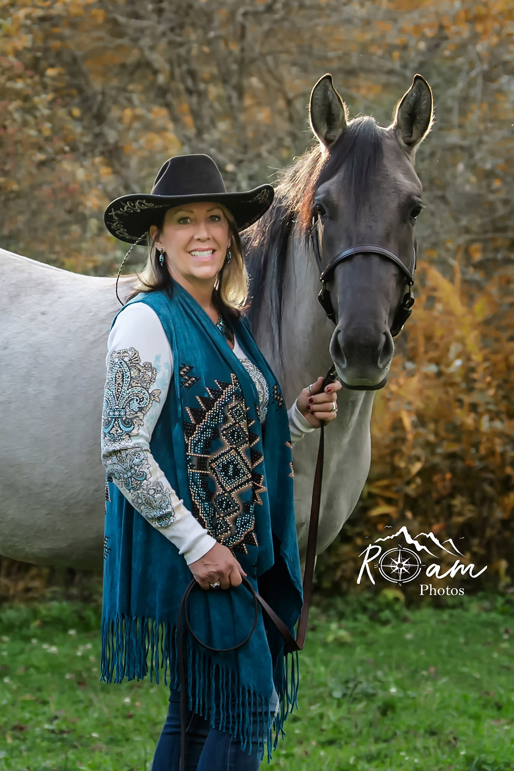 Beautiful cowgirl standing with her quarter horse.