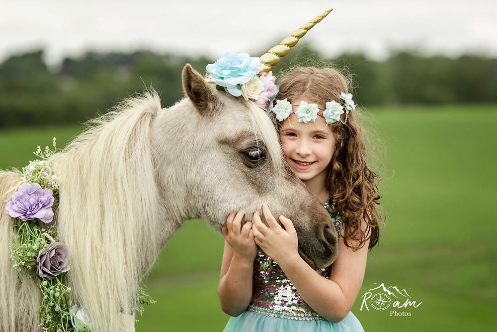 Little girl with flower headband hugging the pony unicorn