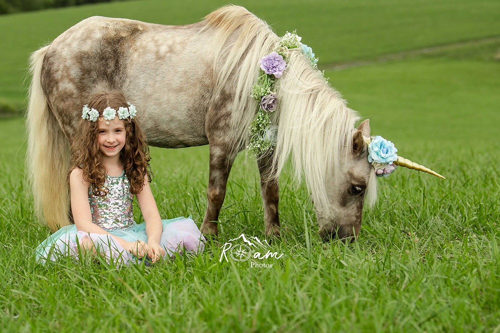 Little girl smiling sitting in the grass with a pony while it eats