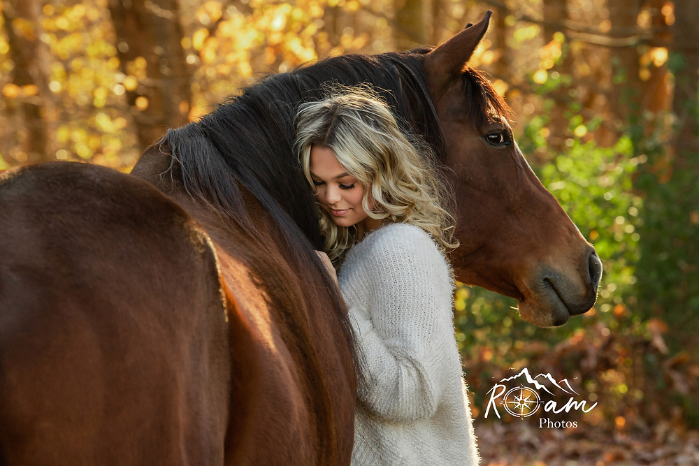 Beautiful young girl snuggling up to her horse.
