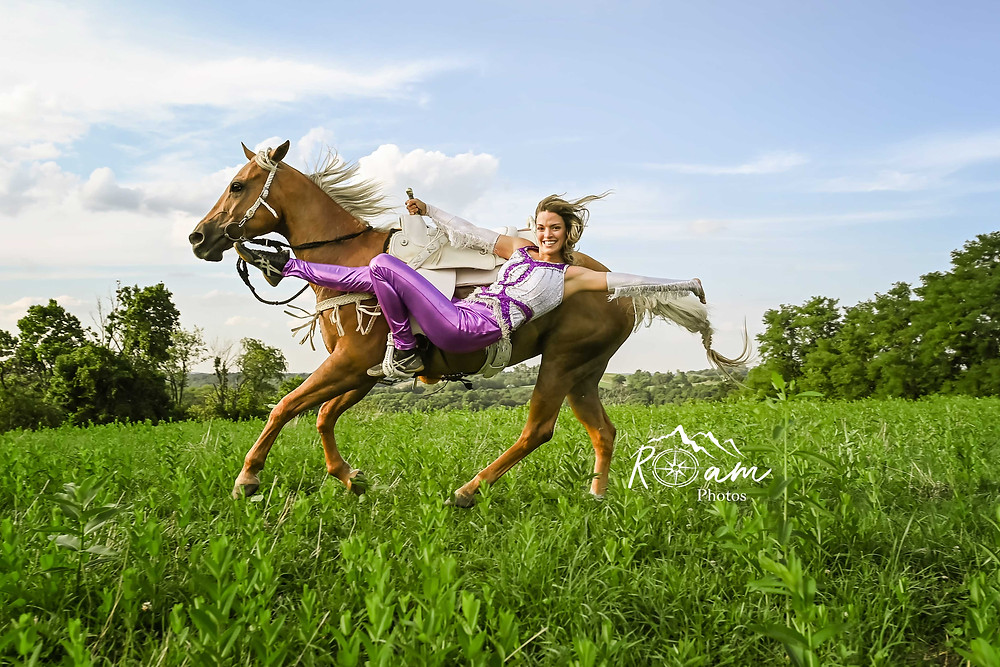 Beautiful girl hanging off side of her horse trick riding