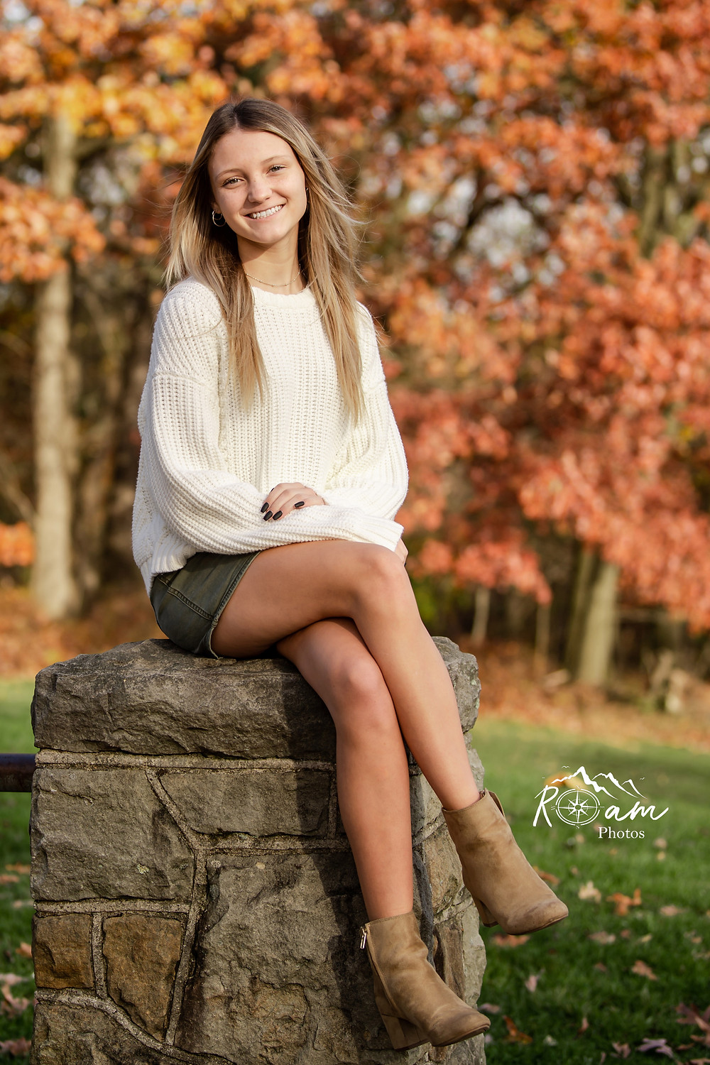Beautiful senior girl sitting on a pillar smiling