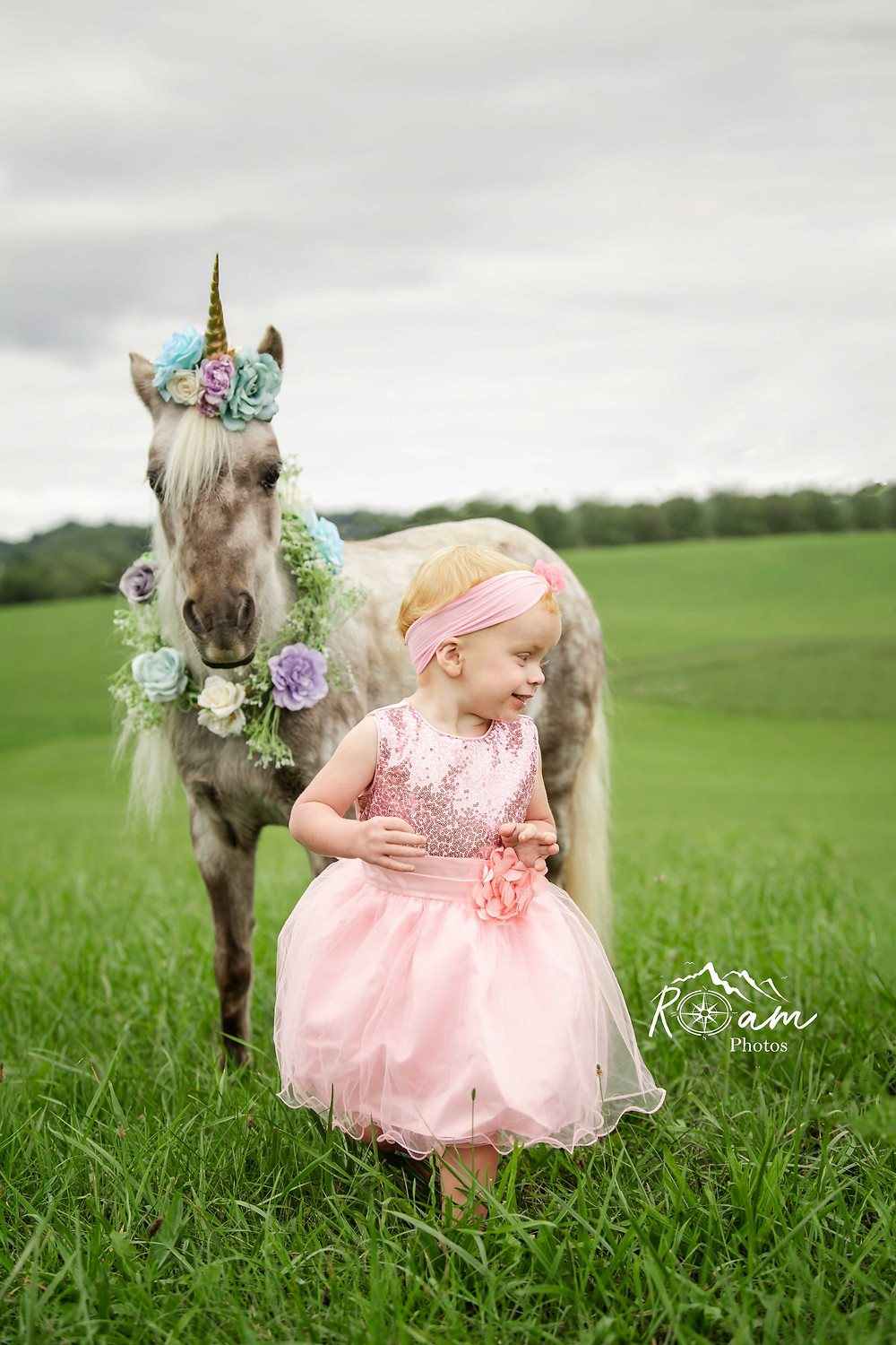 Little girl laughing running away from pony