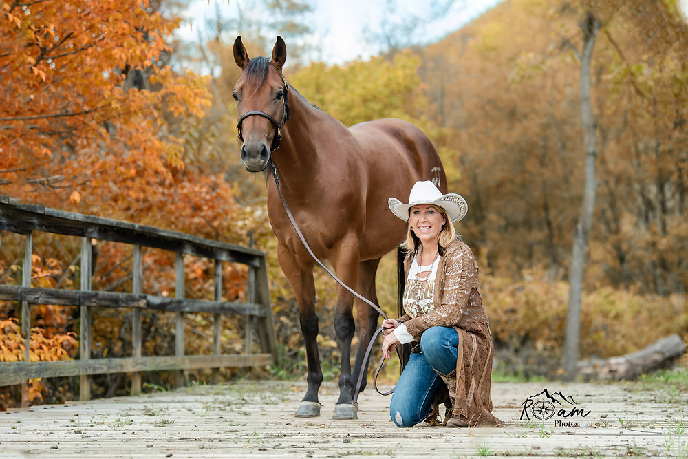 Cowgirl holding her horse in the fall