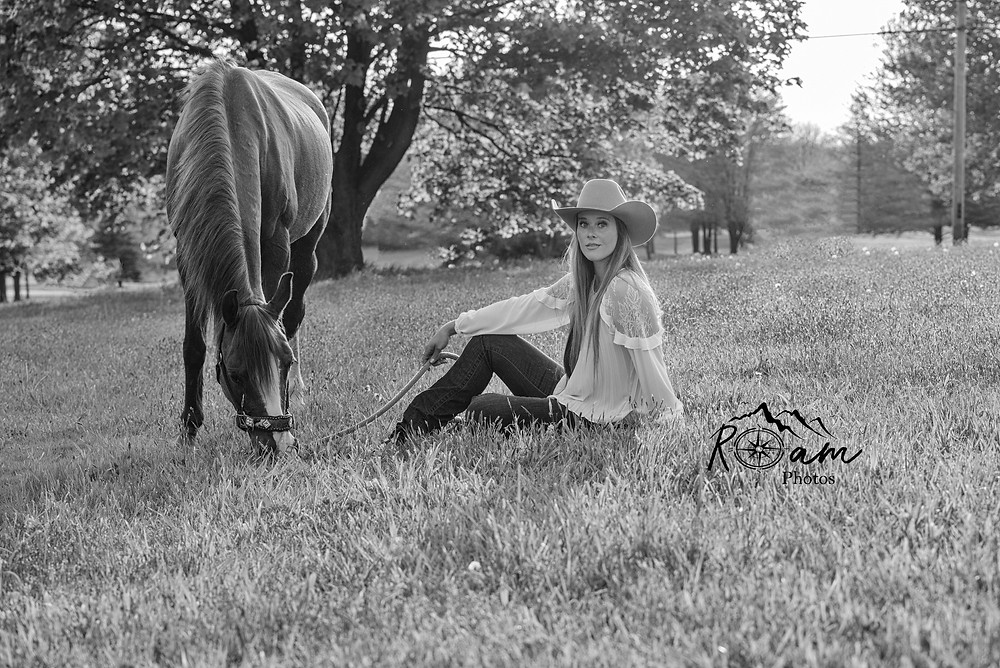 Cowgirl sitting in grass with horse.