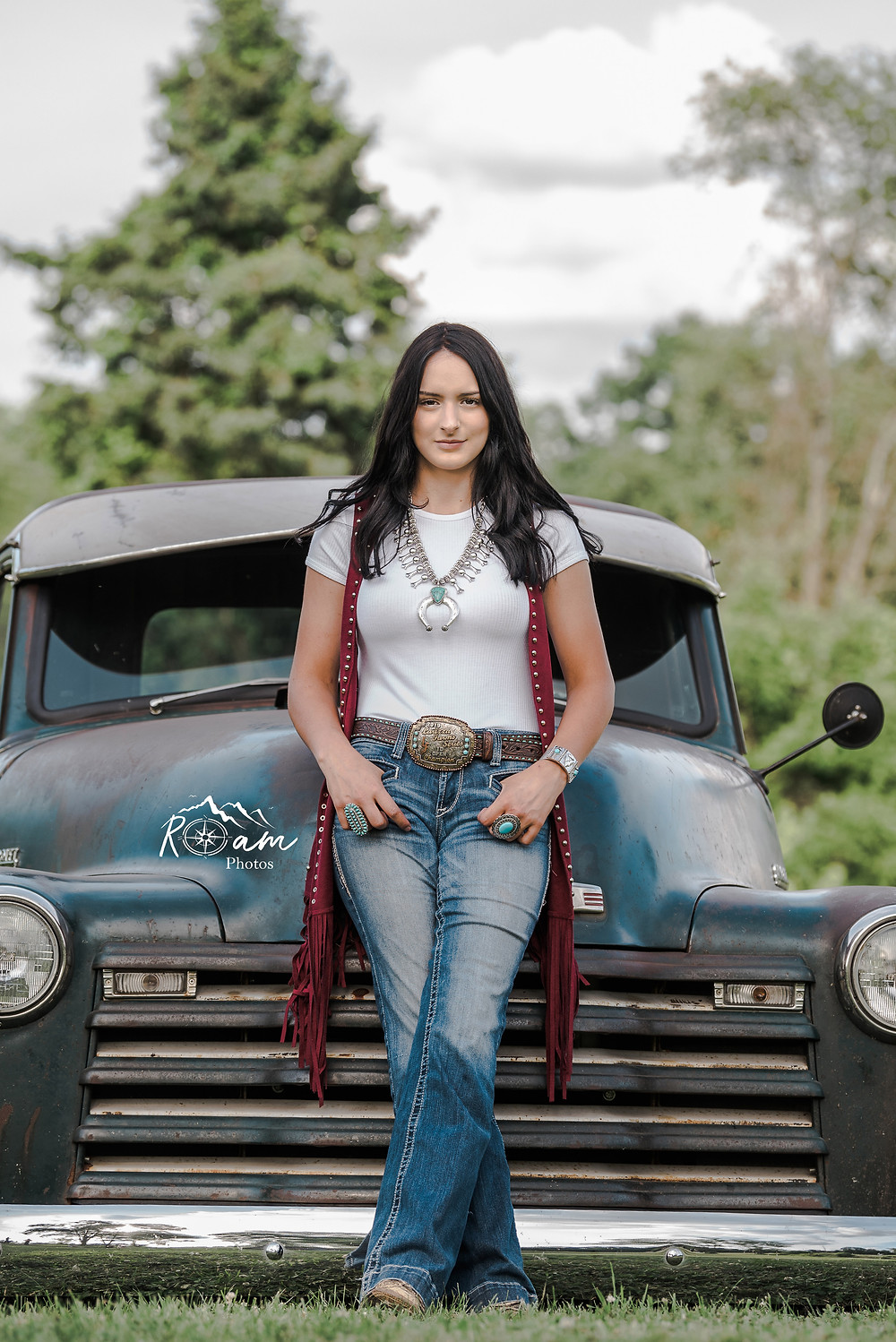 Cowgirl leaning against an old truck.