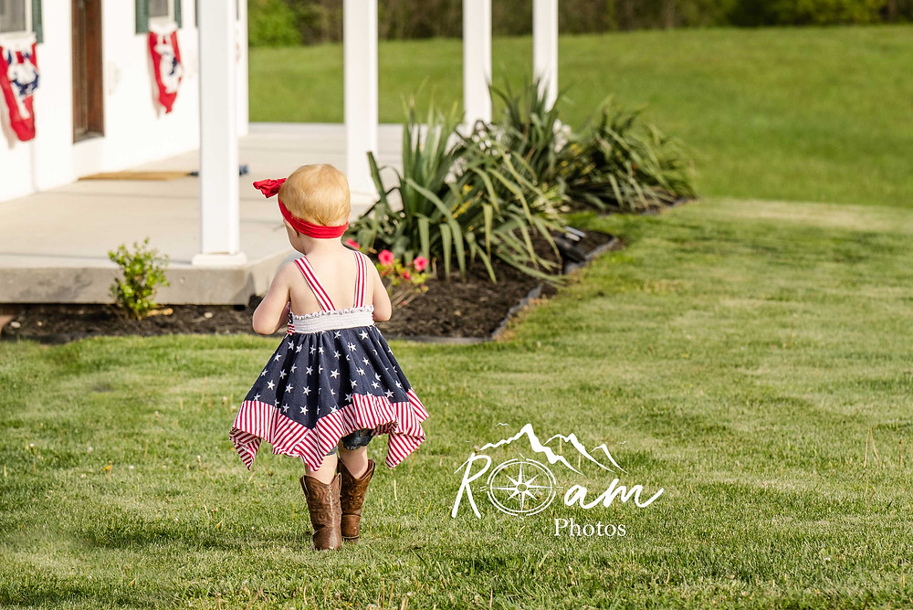 Little girl in cowboy boots and patriotic dress in yard.