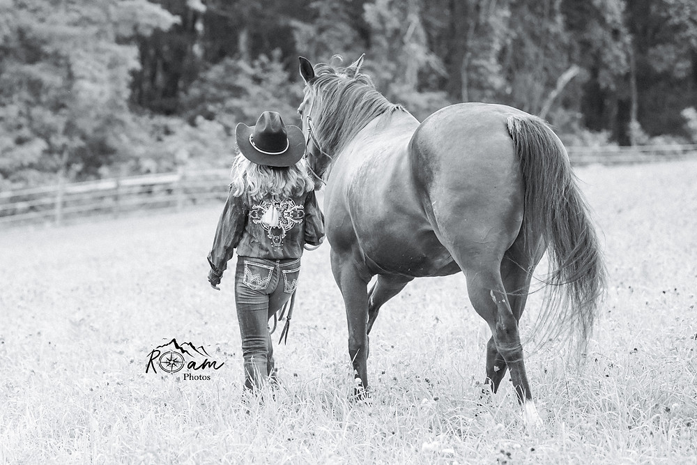 Little cowgirl walking her horse in a field.