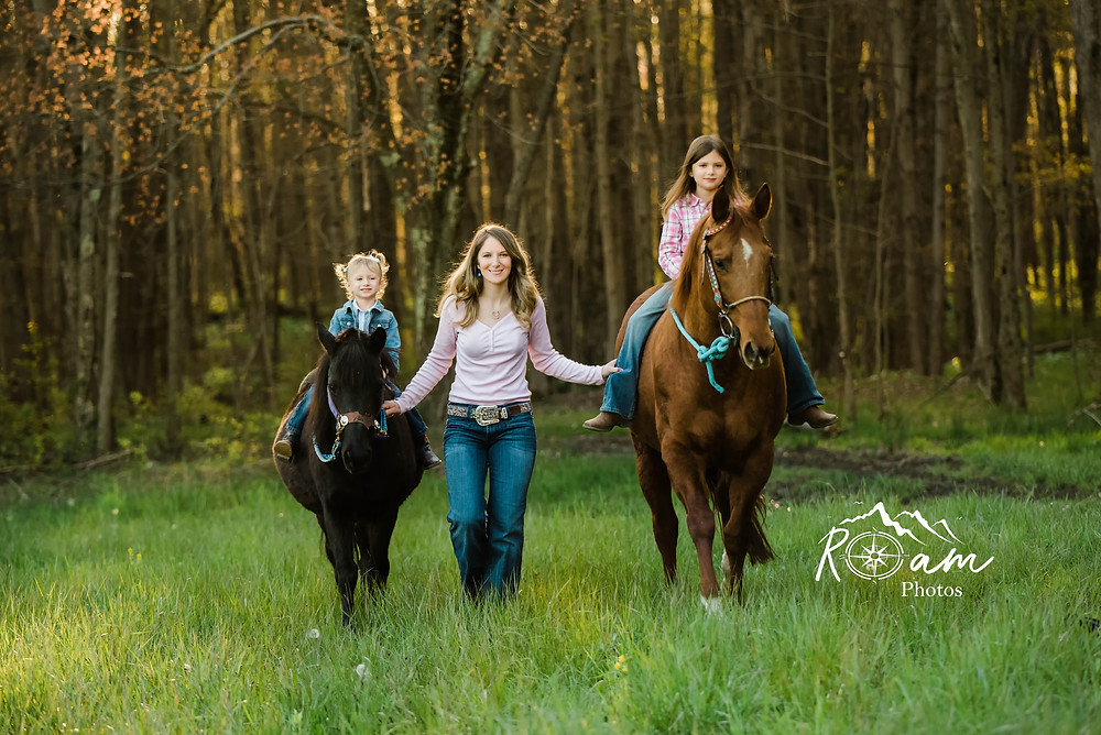 Mom walking with her children as they ride their ponies