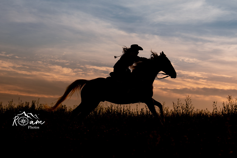 cowgirl running into sunset on horse