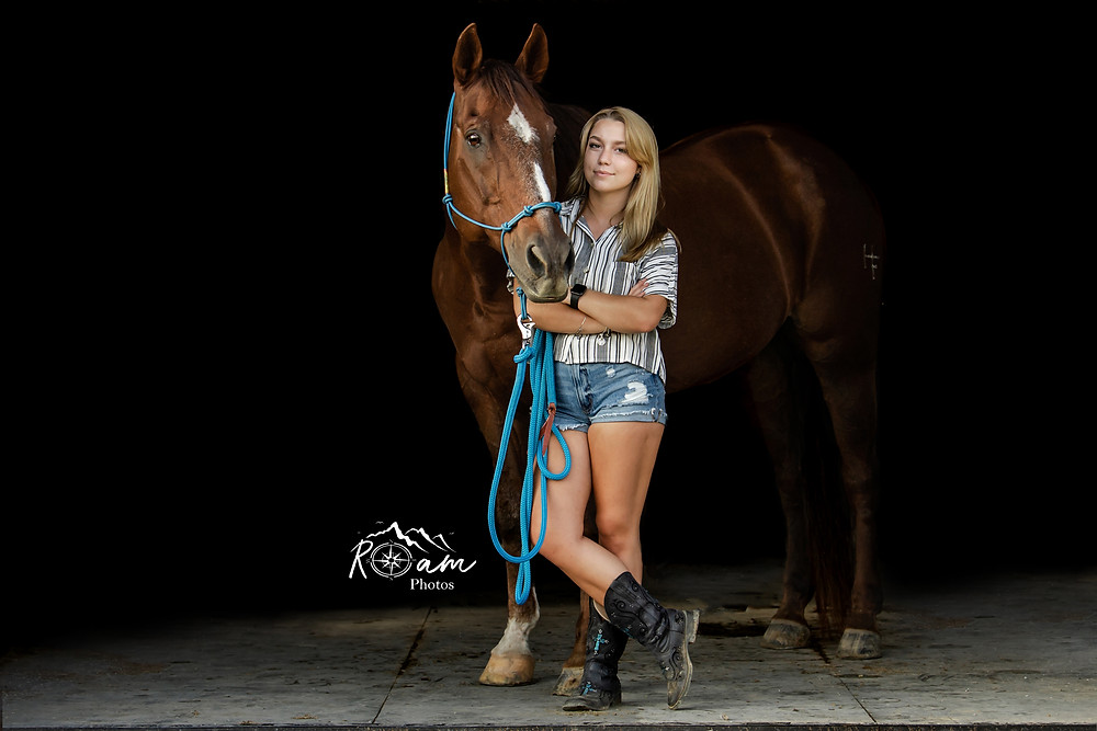 Beautiful cowgirl in shorts and boots standing by her horse.