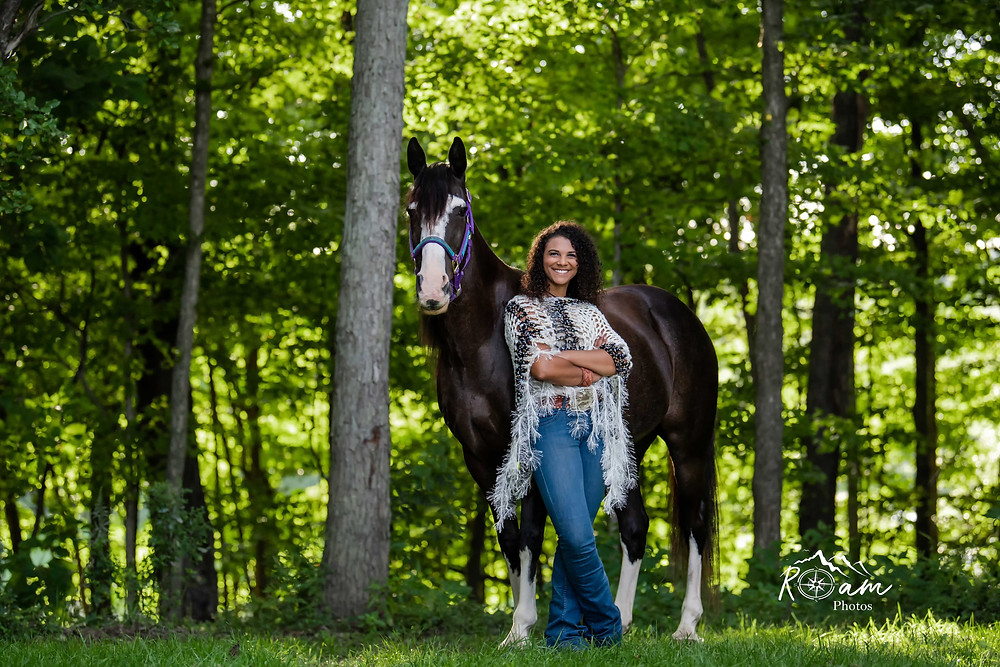 young african american woman standing with arms crossed with her horse
