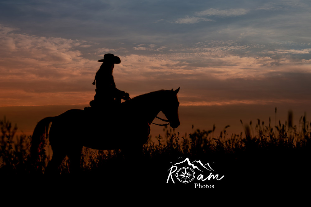 cowgirl walking off into sunset on her horse