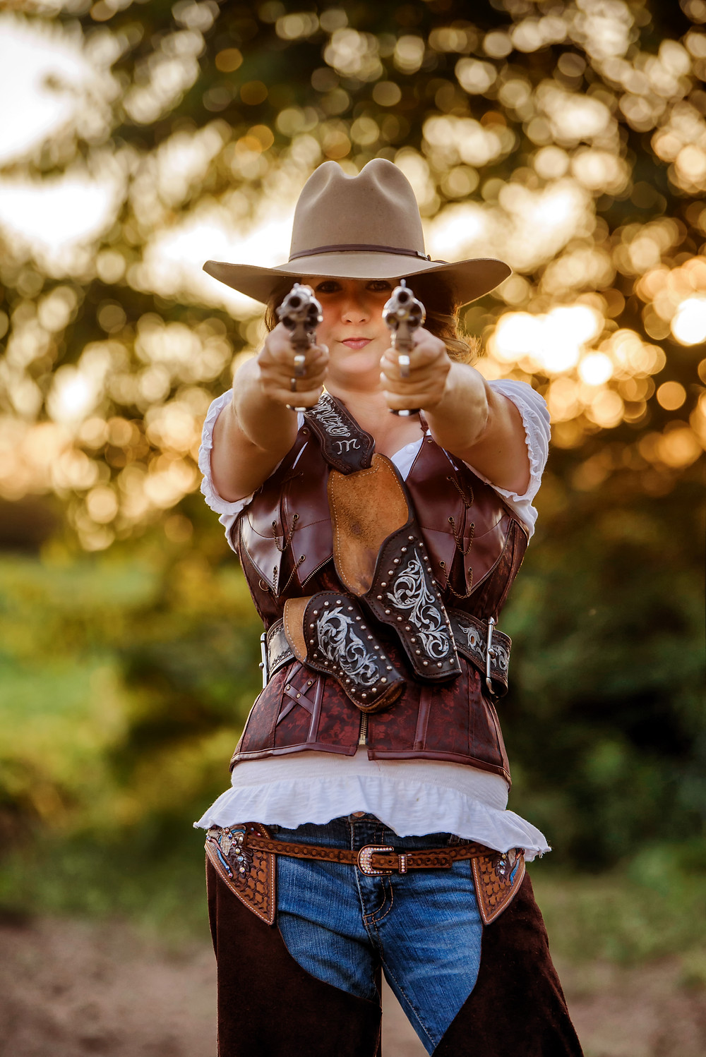 Cowgirl pointing two guns at the camera.