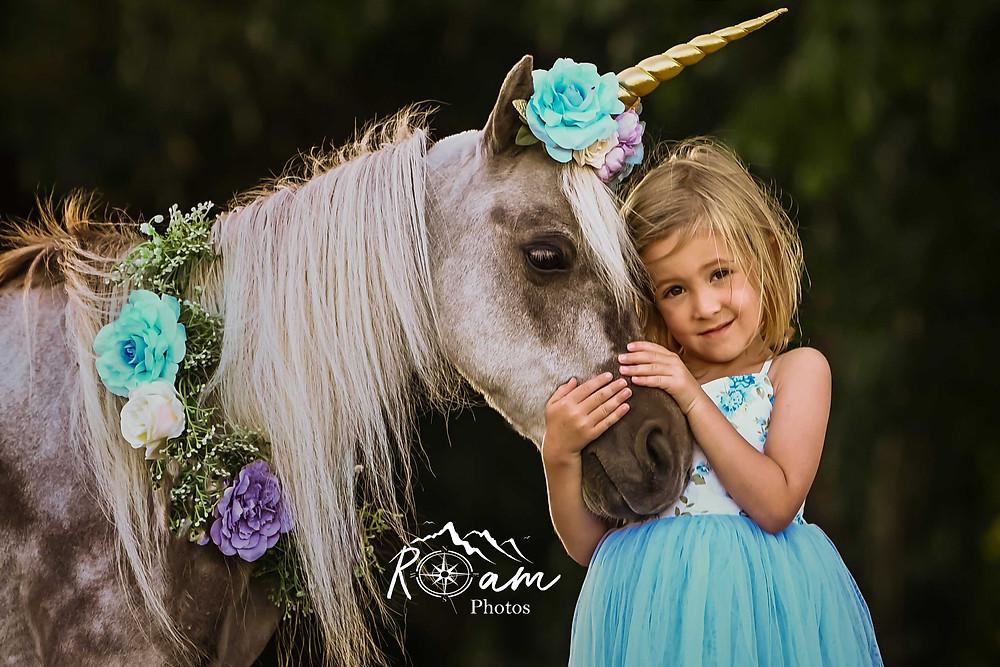 Little girl hugging a pony unicorn