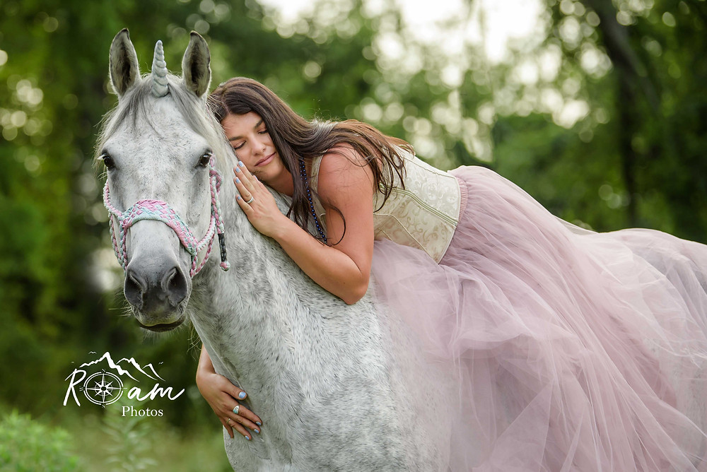 beautiful woman laying on a white unicorn in a pink dress