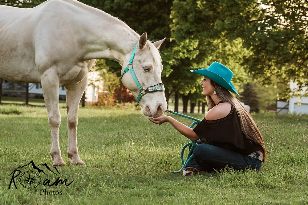 Cowgirl sitting in grass with beautiful horse