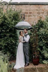 Bride and groom, umbrella, rain, wedding, English wedding, traditional wedding, wedding dress, couple