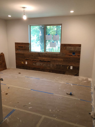 Bedroom under construction with reclaimed wood headboard built in