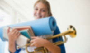 A girl with books, a musical instrument, and a yoga mat