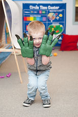 Preschool age boy playing dinosaurs at KidsCentre preschool