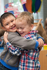 Two children hugging at KidsCentre preschool