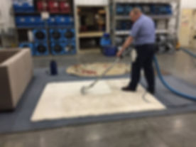 Man cleaning a carpet with professional equipment in Stanton, MI