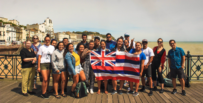 Young people on pier holding Hawaiian flag