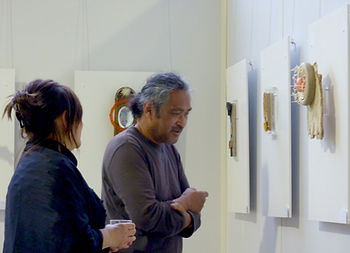 Raymond-bakker of gallery Oost 99 looks at my work on the art fair Artzaanstad.
