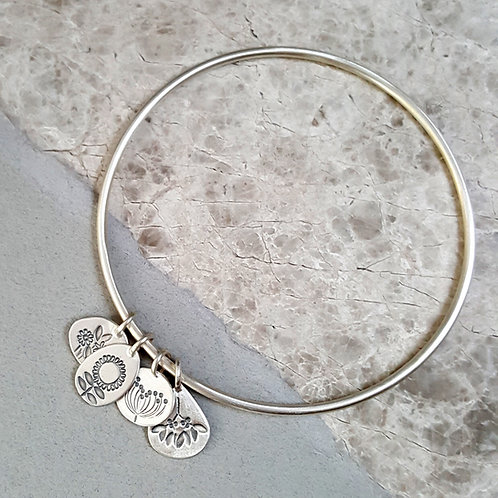 Solid silver charm bangle with four seasons charms